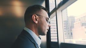 Uomo moderno che discende dall'elevatore con le pareti trasparenti Uomo di affari in ascensore video d archivio