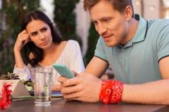 Uomo moderno che indossa la banda di polso floreale rossa facendo uso del suo Smart Phone fotografie stock