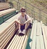 Uomo moderno dei pantaloni a vita bassa della foto d'annata che riposa sul banco Immagini Stock Libere da Diritti