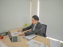 Uomo moderno di affari che lavora molto occupato sul suo scrittorio immagini stock libere da diritti