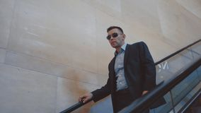 Uomo moderno in vestito alla moda ed occhiali da sole che vanno gi? sulla scala mobile archivi video