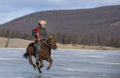 Uomo mongolo che monta un cavallo su un lago congelato Khovsgol immagini stock
