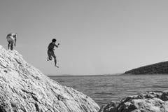 Uomo monocromatico che salta giù roccia nell'acqua sconosciuta Fotografie Stock Libere da Diritti