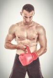 Uomo muscolare adatto che mette i suoi guantoni da pugile davanti alla macchina fotografica Immagine Stock