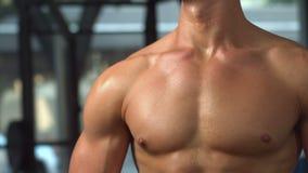 Uomo muscolare adatto che posa altrimenti e che guarda archivi video
