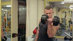 Uomo muscolare adatto che si esercita con la testa di legno stock footage