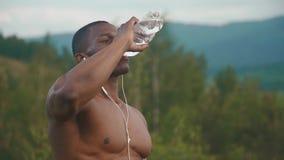 Uomo muscolare afroamericano esaurito con l'acqua potabile del torso nudo dopo la formazione di sport all'aperto Montagna verde stock footage