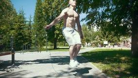 Uomo muscolare atletico che salta con una corda, allenamento all'aperto al giorno soleggiato - rallentatore stock footage