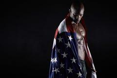 Uomo muscolare avvolto nella bandiera americana con lo spazio della copia Fotografia Stock