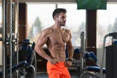 Uomo muscolare bello che flette i muscoli in palestra immagine stock