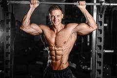 Uomo muscolare bello del culturista che fa gli esercizi in palestra Immagine Stock