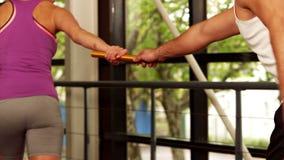 Uomo muscolare che dà il bastone al suo partner video d archivio