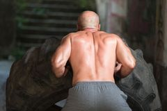 Uomo muscolare che esercita allenamento di Crossfit dalla vibrazione della gomma Fotografia Stock Libera da Diritti