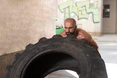 Uomo muscolare che esercita allenamento di Crossfit dalla vibrazione della gomma Immagine Stock