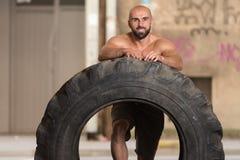 Uomo muscolare che esercita allenamento di Crossfit dalla vibrazione della gomma Immagini Stock Libere da Diritti