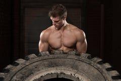 Uomo muscolare che esercita allenamento di Crossfit dalla vibrazione della gomma Immagini Stock