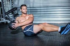 Uomo muscolare che fa esercizio con palla medica Fotografie Stock Libere da Diritti