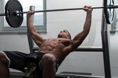 Uomo muscolare che fa esercizio della stampa di banco per il petto Fotografia Stock