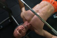 Uomo muscolare che fa esercizio della stampa di banco per il petto Immagini Stock
