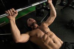 Uomo muscolare che fa esercizio della stampa di banco per il petto Immagini Stock Libere da Diritti