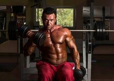 Uomo muscolare che fa esercizio pesante per il bicipite Fotografia Stock Libera da Diritti