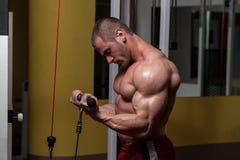 Uomo muscolare che fa esercizio pesante per il bicipite Fotografie Stock Libere da Diritti