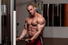 Uomo muscolare che fa esercizio pesante per il bicipite Immagini Stock