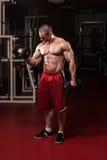 Uomo muscolare che fa esercizio pesante per il bicipite fotografia stock