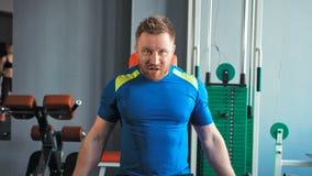 Uomo muscolare che fa gli esercizi con le teste di legno ai bicipiti in palestra stock footage