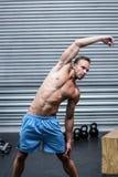 Uomo muscolare che fa gli stretchings del braccio Fotografie Stock