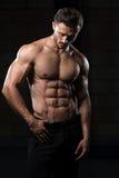 Uomo muscolare che flette i muscoli in palestra Immagine Stock Libera da Diritti