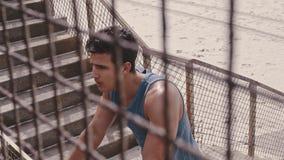 Uomo muscolare che prende una rottura dopo l'allenamento sulla spiaggia stock footage