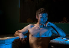 Uomo muscolare che propone nella piscina Immagine Stock