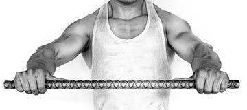 Uomo muscolare che prova a piegare una barra di ferro Fotografia Stock Libera da Diritti