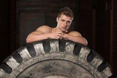 Uomo muscolare che riposa dopo l'allenamento della gomma Fotografie Stock