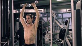 Uomo muscolare che risolve con i dumbbells stock footage