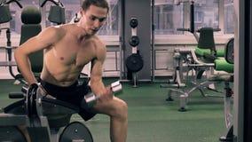 Uomo muscolare che risolve con i dumbbells video d archivio