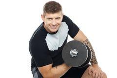 Uomo muscolare che risolve con il barbell Fotografia Stock Libera da Diritti