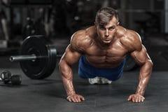 Uomo muscolare che risolve nella palestra che fa gli esercizi di spinta-UPS, forte ABS nudo maschio del torso immagini stock