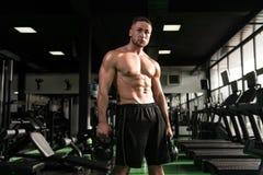 Uomo muscolare che si esercita con la Bollitore-campana Fotografie Stock