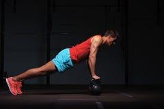 Uomo muscolare che si esercita con le campane del bollitore in palestra Fotografie Stock