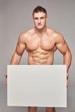 Uomo muscolare che tiene insegna bianca con lo spazio della copia fotografie stock libere da diritti
