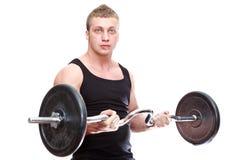 Uomo muscolare con il barbell in mani Immagini Stock