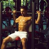 Uomo muscolare con il bilanciere fotografia stock