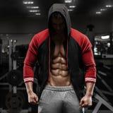 Uomo muscolare con l'ABS rivelante del rivestimento aperto in palestra, allenamento Addominale a forma di immagine stock libera da diritti