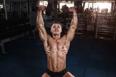 Uomo muscolare del culturista dell'atleta che fa gli esercizi con le teste di legno Fotografia Stock