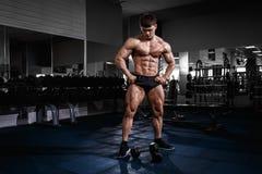 Uomo muscolare del culturista dell'atleta che posa con le teste di legno in palestra Fotografia Stock Libera da Diritti