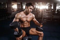 Uomo muscolare del culturista dell'atleta che posa con le teste di legno in palestra Fotografia Stock
