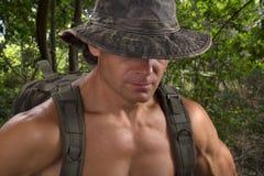 Uomo muscolare di avventura in cappello di camo che fa un'escursione nella giungla immagini stock libere da diritti