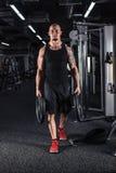 Uomo muscolare durante l'allenamento nella palestra Immagini Stock